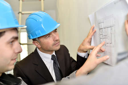 controling: Supervisor with construction worker checking blueprint
