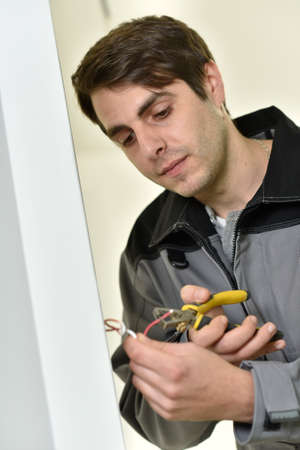 controling: Electrician cutting wire to prepare installation
