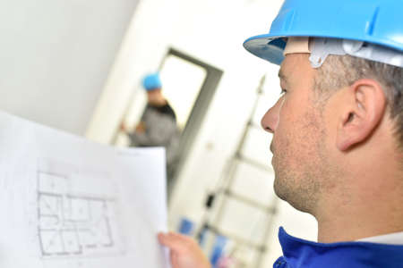 controling: Builder on site checking construction blueprint