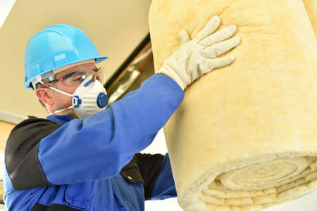 fiberglass: Hombre que sostiene rollos lana de vidrio en casa de nueva construcción Foto de archivo