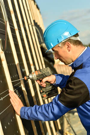 artisan: Construction worker using electric drill on building site Stock Photo