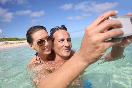 Couple in Caribbean sea taking picture of themselves Stock Photo