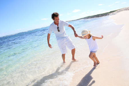 Father and little girl playing together at the beach photo