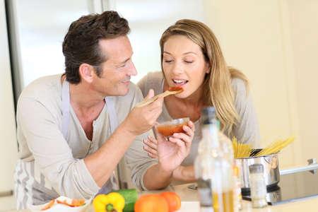 marido y mujer: Hombre que tiene la mujer degustaci�n de salsa de tomate Foto de archivo