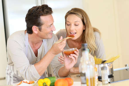 Man having woman tasting tomato sauce Stock Photo