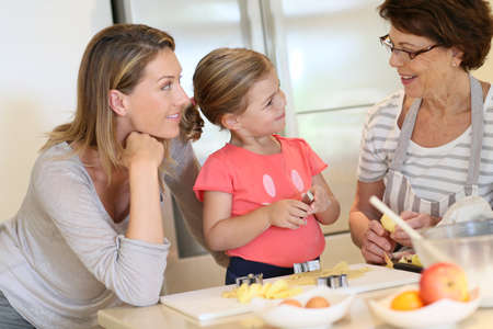 Little girl with mom and grandmother baking cookies at home photo