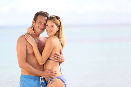 bikini couple: Loving couple in swimsuit embracing at the beach