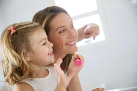 toothcare: Mother and daughter in bathroom brushing her teeth Stock Photo