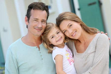 Portrait de famille heureuse debout devant la maison