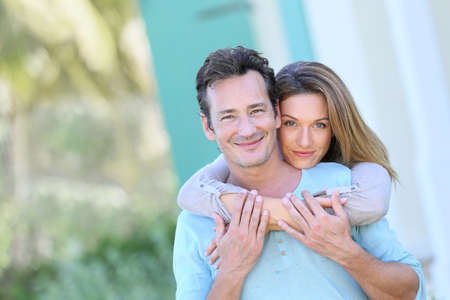 40 to 45 years old: Middle-aged couple embracing in front of house