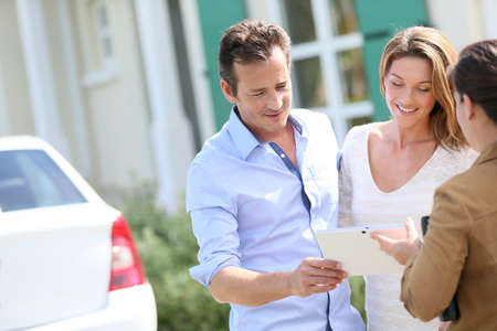 realtor: Couple meeting real-estate agent outside new property