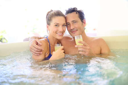 hot: Romantic couple drinking cahmpagne in hot tub