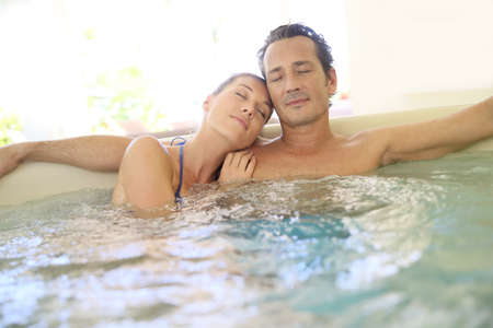 woman in bath: Romantic couple relaxing with eyes shut in jacuzzi Stock Photo