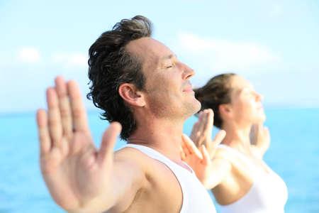 Paar doen yoga en ontspanningsoefeningen aan zee