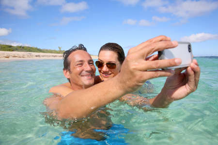 Couple in Caribbean sea taking picture of themselves photo