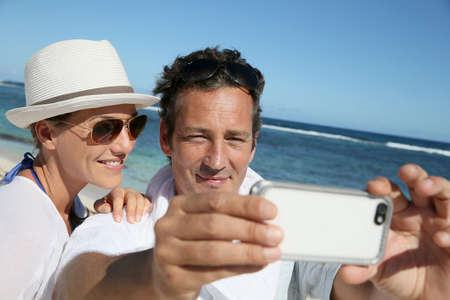 Couple at the beach making a selfy with smartphone photo