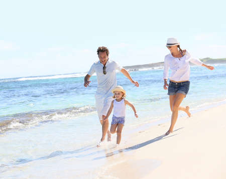 Couple with little girl running on Caribbean beach photo