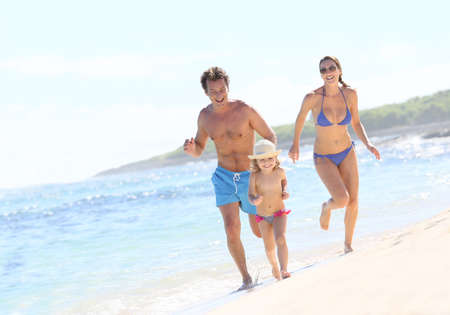 Family running in swimsuit on a Caribbean beach photo