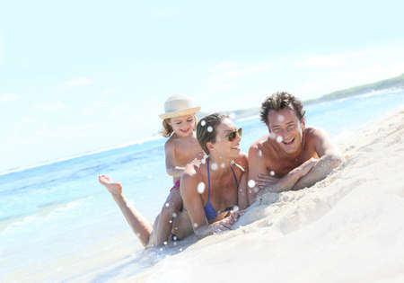 Happy family laying on a sandy beach Stock Photo