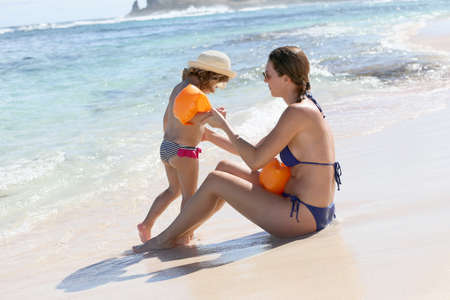 armbands: Mother putting swimming armbands to little girl at the beach