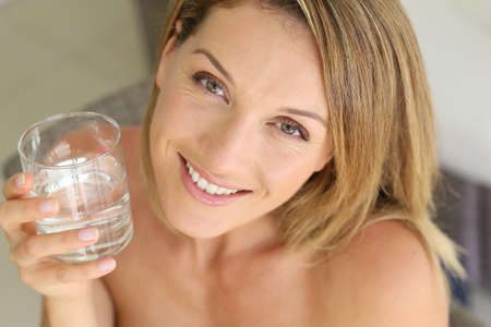 35 years old: Portrait of blond woman holding glass of water