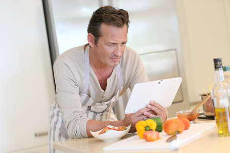 45 years old: Handsome man in kitchen looking at digital tablet for recipe
