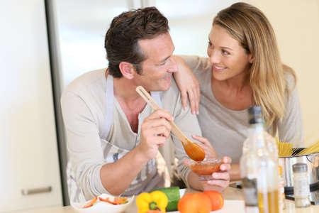 Woman watching husband preparing pasta dish photo