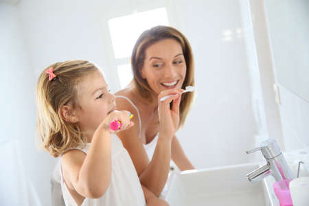 brushing: Mother and daughter in bathroom brushing her teeth Stock Photo