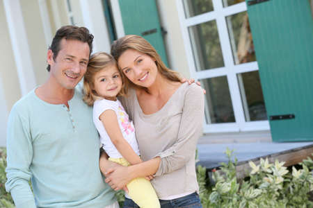 Portrait of happy family standing in front of house