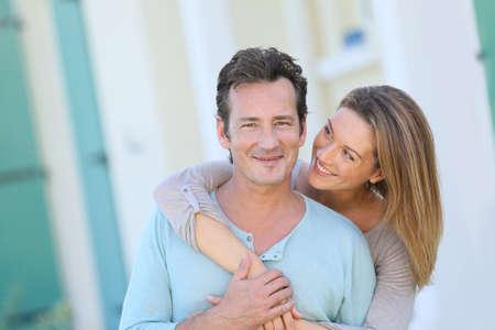 parejas felices: De mediana edad joven abrazando en frente de la casa