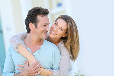 attraktiv: Paar mittleren Alters umarmt vor dem Haus