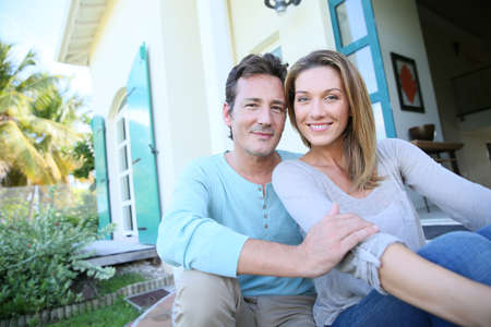 front house: Middle-aged couple sitting on house front door