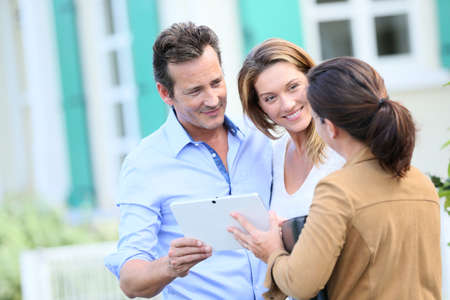 realestate: Couple meeting real-estate agent outside new property