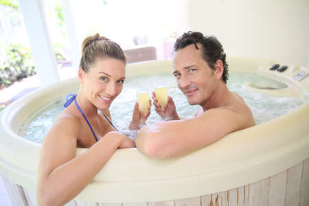 wife of bath: Romantic couple drinking cahmpagne in hot tub