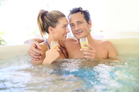 hot tub: Romantic couple drinking cahmpagne in hot tub