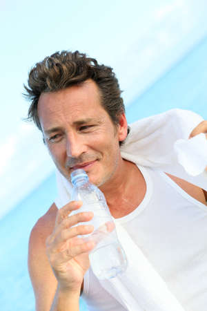 Handsome man drinking water from bottle after exercising photo