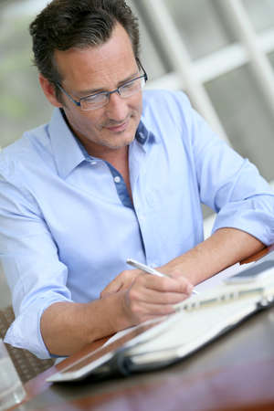 40 years old man: Businessman with eyeglasses writing notes on paper Stock Photo