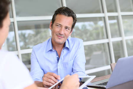 Closeup of businessman having client signing contract on tablet photo