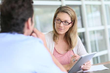 reuniones empresariales: Empresaria en la reuni�n de negocios que usa la tableta