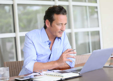 uomini maturi: Uomo che lavora da casa sul computer portatile Archivio Fotografico