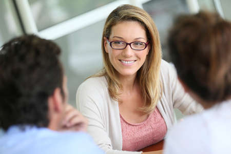 Businesswoman meeting with couple to sign financial contract Stock Photo