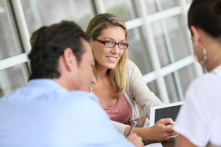 Realtor: Businesswoman meeting with couple to sign financial contract Stock Photo