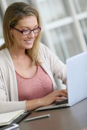 Middle-aged woman working from home on laptop
