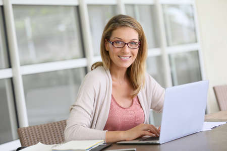 Mujer de mediana edad que trabaja desde su casa en la computadora portátil