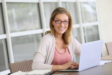 trabajando en computadora: Mujer de mediana edad que trabaja desde su casa en la computadora port�til Foto de archivo