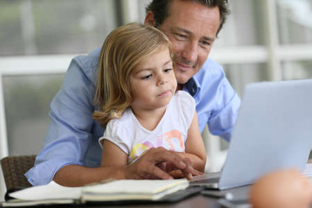 father teaching daughter: Man with daughter looking at internet on laptop