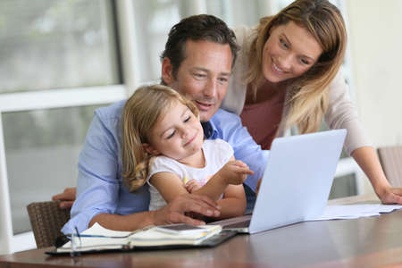 Parents with little girl looking at pictures on computer photo