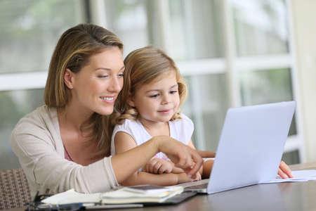 madre trabajando: Ni�a mirando el ordenador port�til con su mam� Foto de archivo