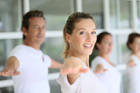 40s adult: Attractive blond woman attending yoga course with group