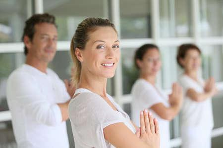 Aantrekkelijke blonde vrouw bijwonen yoga cursus met groep